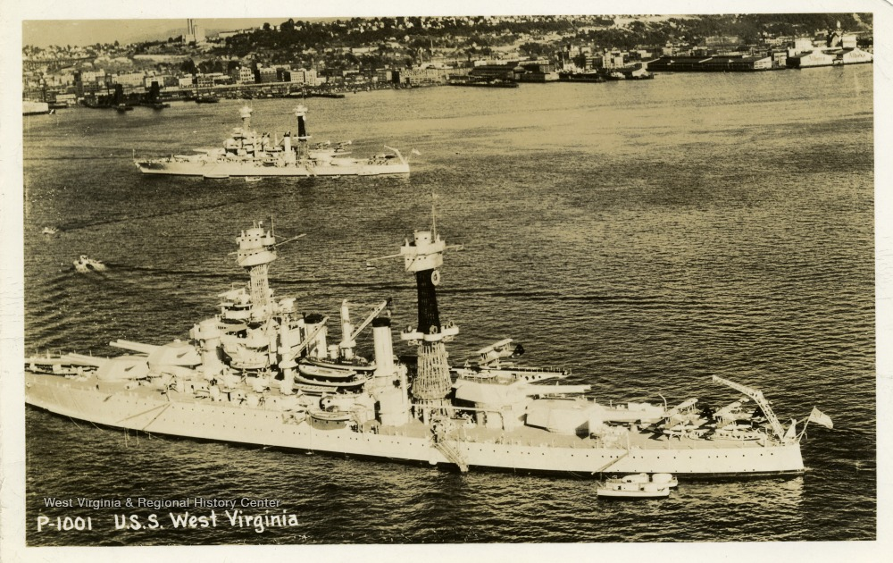 Postcard of the U.S.S. West Virginia at sea outside of a city. The photograph was taken before 1941.