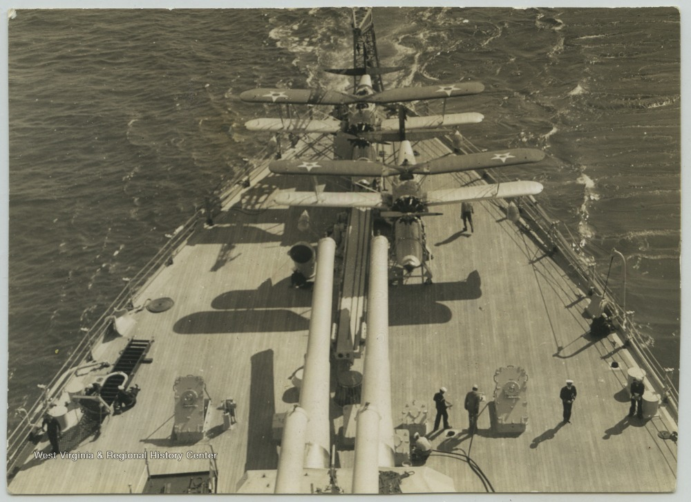 Crew members walk around the deck while the ship is at sea.