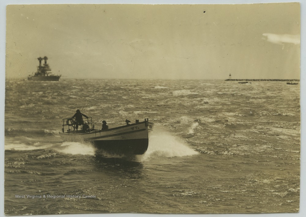 A boat speeds across the sea while the U.S.S. West Virginia lurks in the background.