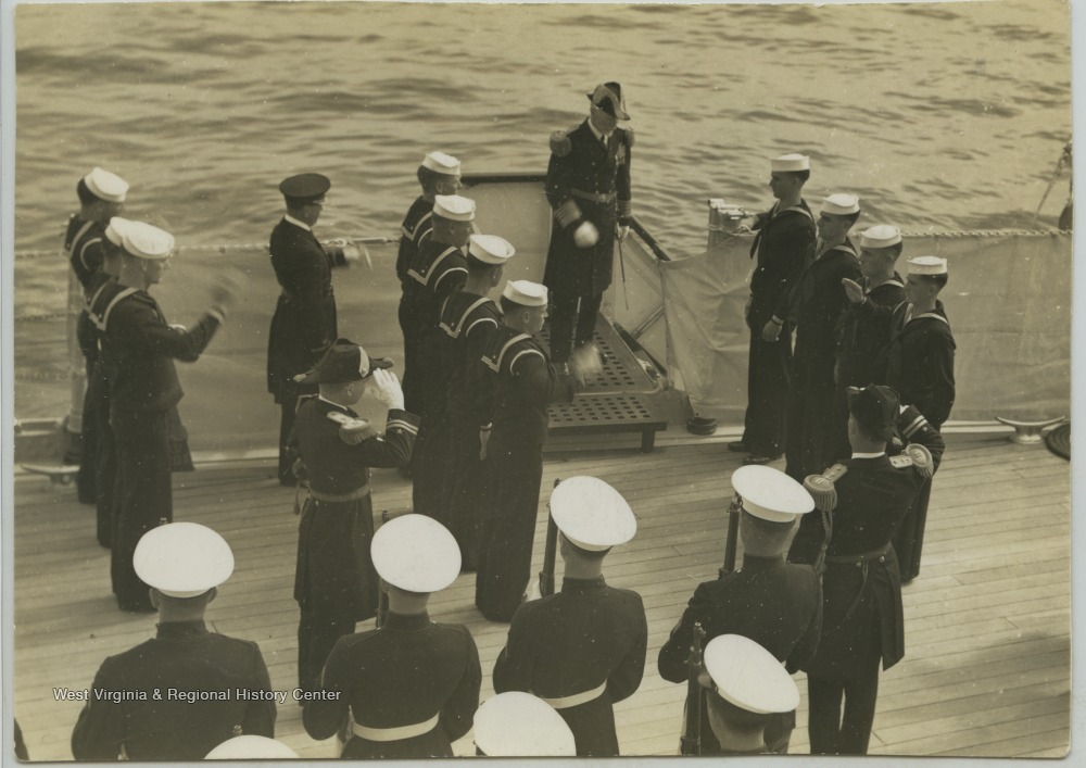 The admiral is greeted with a band and guard as he boards the ship.