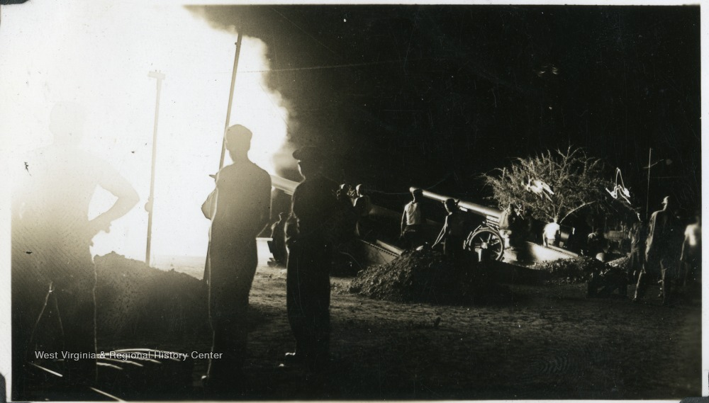 A group of soldiers gather around coastal artillery during a defense campaign. Photograph taken from a U.S.S. West Virginia scrapbook.