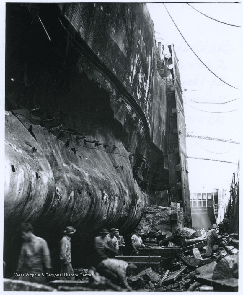 Crew members during a salvage and repair operation work port side of the battered battleship. The U.S.S. West Virginia was hit by seven torpedoes and two bombs during the December 7th attack.