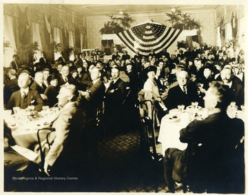 Men and women dining in celebration of the U.S.S. West Virginia.