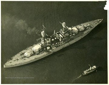 The U.S.S. West Virginia next to another much smaller boat. Stamped on back: Official photograph. Not to be used for publication by order of the Chief of the Bureau of Aeronautics.