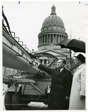 Barron touches the U.S.S. West Virginia mass. The capitol building stands in the background.