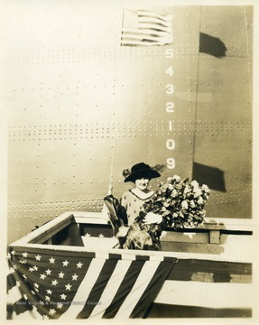 Mann is pictured with a bouquet of roses in front of the ship.