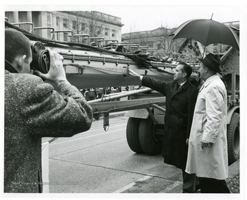 A photographer captures the moment when Governor Barron touches the U.S.S. West Virginia mast outside of the capitol building.