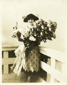 Portrait of Alice Wright Mann holding a bouquet and a bottle prior to the christening of the U.S.S. West Virginia.