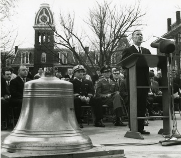 Military officers listen as Joseph Gluck speaks at dedication of the bell from the 'West Virginia' outside Oglebay Hall. In the background is Woodburn Hall.