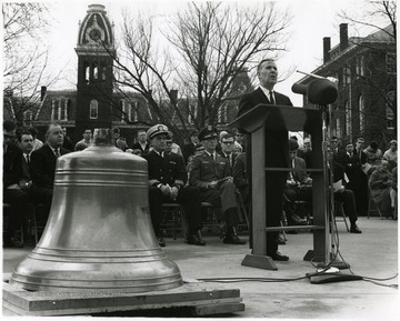 'Rev. Joe Gluck speaks at Dec. 7, 1967 dedication ceremonies for the bell from the armored cruiser 'U.S.S. West Virginia.'  Two other main speakers are shown seated in the first row: WVU President James B. Harlow (second from left) and Naval Reserve Captain Marlyn E. Lugar (third from left).