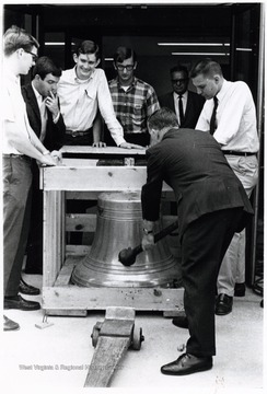With assistance from members of Alpha Phi Omega, a service fraternity, Joe Gluck helps unpack the bell of battle cruiser West Virginia:  Doug Ritchey (left); John Liston (right); Dan Blosser (third from left).