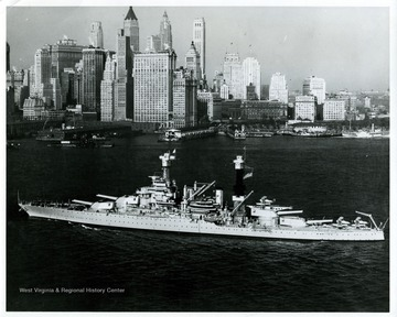 An aerial oblique view of U.S.S.  West Virginia in East River, with New York City in background.