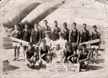 A group of men in swimsuits and holding oars pose together for a group photo.