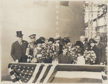 Miss Alice Wright-Mann, third from left holding a large bouquet and bottle, poses with a group on the battleship. The rest of the subjects are unidentified.Alice Wright-Mann, of Mercer County, sponsored the battleship which was built by the Newport News Shipbuilding and Drydock Co. of Newport News, Va. Wright-Mann was the daughter of a millionaire coalmine operator, Isaac T. Mann.