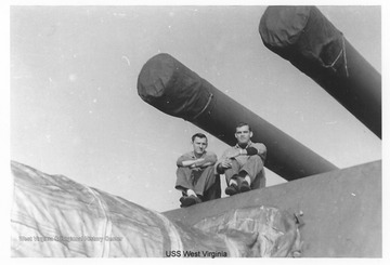 The two men in the photo are sitting on top of or near one of the gun turrets on the ship.  Photos are from an album belonging to a crew member of the U.S.S. West Virginia.  William Wright, Radio Technician 2C, was on the ship from 1944-45 and saw action at Leyte Gulf, Iwo Jima, and Okinawa.