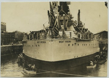 Crew members surround the battleship as its anchored near the dock.