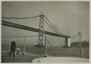 A sailor walks along the deck while the ship passes the bridge.