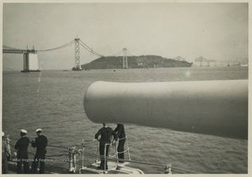 Sailors idle beneath the ship's gun barrel while passing the bridge.