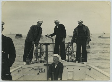 A crew consisting of a cox, and engineer and two extra men are pictured on the stem of the boat, which was used to take enlisted men ashore. The boat carries about 125 men and is 50 feet long.