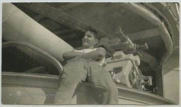 "An unidentified crew member leans against the 5"" gun and port."
