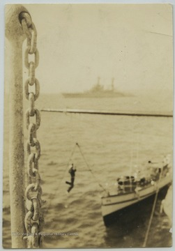 A sailor is transferred to the motor boat by gliding down a rope and pulley system. Motor boats were used to carry enlisted men ashore. Photo taken from the deck of the U.S.S. West Virginia. An unidentified battleship lurks in the background.