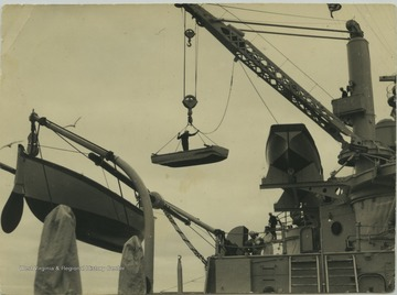"A sailor stands in the boat while it's being raised by the battleship's crane. The ""punt"" boat was used only to paint the sides of the ship. The boat pictured on the far left is a whale boat, which is used as a life boat and is also used in racing. The boat on the right  is called a ""racing cutter"" and is also used as a life boat and in cutter racing."