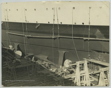 A group of men are scattered along the dry dock inspecting and repairing the ship.