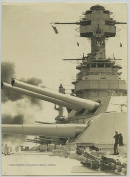 Two sailors on the deck observe the gunfire.
