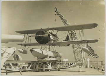 The plane sits on the battleship's deck.