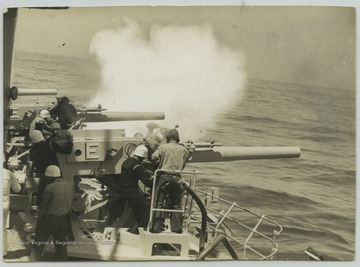 "Crew members fire the 5"" guns."