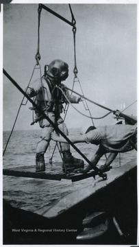 A sailor prepares to dive into the sea off the deck of the U.S.S. West Virginia.