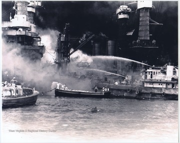Men on boats attempt to extinguish the fire on the U.S.S. West Virginia.