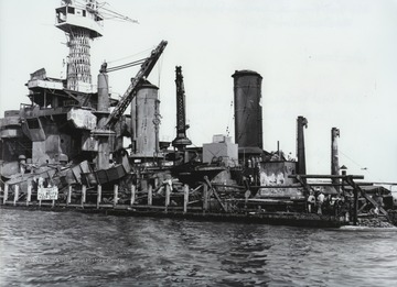 "The U.S.S. West Virginia looks battered and wounded while docked at the naval shipyard. The ""Wee Vee"" was hit by nine bombs and torpedoes by the Japanese warplanes during the December 7th attack."