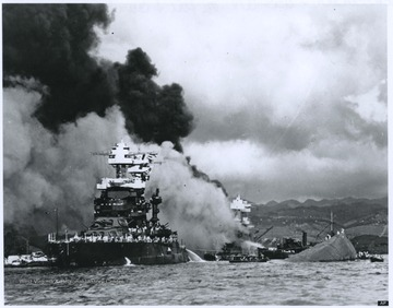 Smoke billows from the U.S.S. West Virginia, which is pictured in the back and center of the photograph. The ship eventually sank.Floating on the left is the U.S.S. Maryland. On the right is a capsized U.S.S. Oklahoma.
