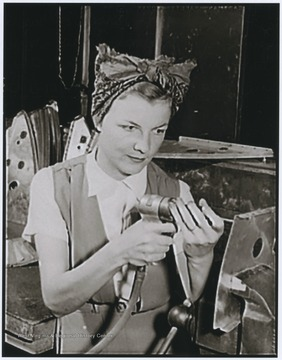 Fern Evan's husband, GM3e Woodrow W. Evans was killed aboard the U.S.S. West Virginia during the Japanese attack on Pearl Harbor on December 7, 1941, leaving Fern to support herself and their 20 month old son.  Subsequently, Mrs. Evans was employed at a West Coast aircraft plant.  She's shown here working on a radio bracket for a bomber.