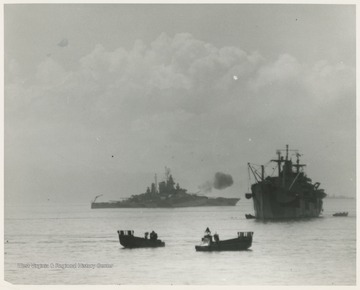 """The guns of U.S.S. West Virginia (BB-48) in operation.  L.C.M.'s in foreground.""  L.C.M. stands for Landing Craft Mechanized."