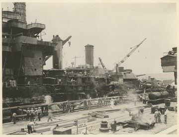 """The W. Va. is shown as she was photographed at a dry dock in Pearl Harbor. The battleship was severely damaged in the Japanese raid Dec. 7, 1941. Damages to her sides are visible."""